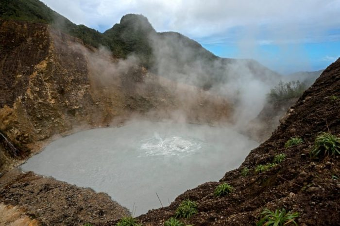 Volcanic Boiling Lake in Dominica, Caribbean Island Nation. After a rigorous hike through rain forest and Desolation Valley hiker is rewarded by a magnificent site of literally boiling lake.