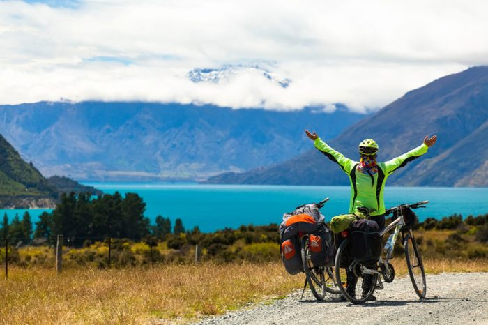 cyclist stands on the winding asphalt mountain road near Lake Pukaki view from Glentanner Park Centre near Mount Cook, on a background of blue sky with clouds, snowy Southern Alps.