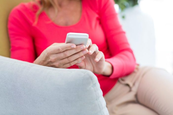 Midsection of woman using mobile phone on couch at home