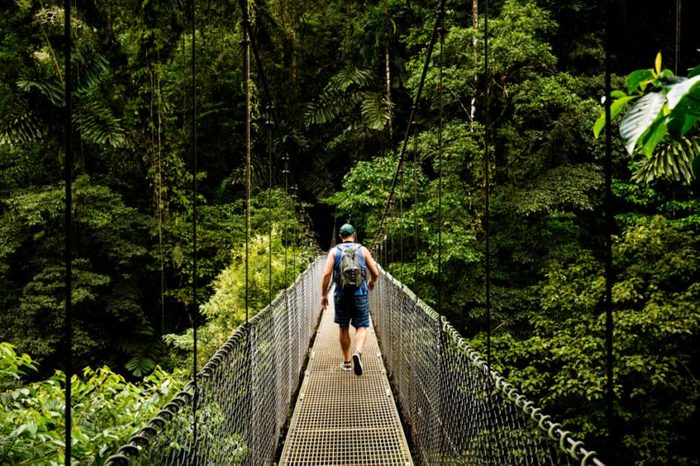Man walking on a hanging bridge in Arenal Volcano National Park - Costa Rica