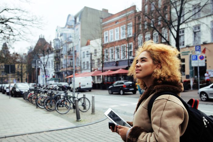 young pretty african american girl with curly hair making photo on a tablet, lifestyle people concept, tourist in european german city