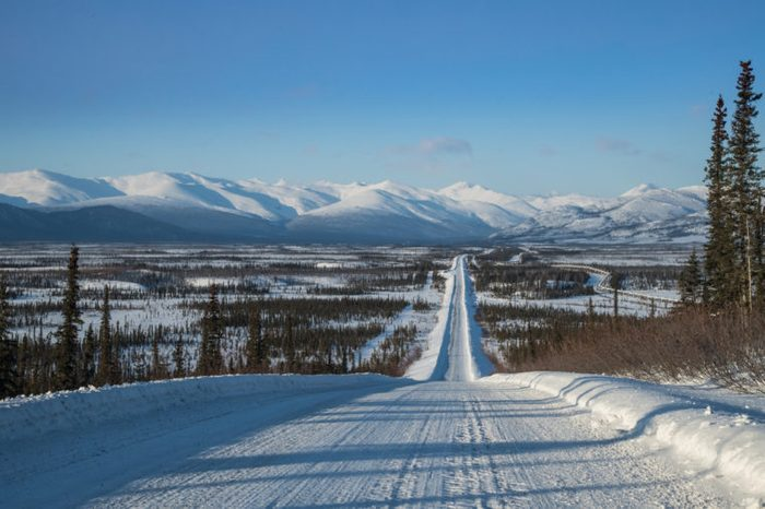 view along dalton highway toward brooks range in north alaska in winter, with oil pipeline seen to right