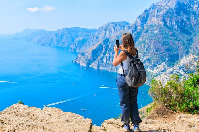 Woman taking photos of beautiful scenery at Path of Gods on Tyrrhenian sea, Amalfi coast, Italy