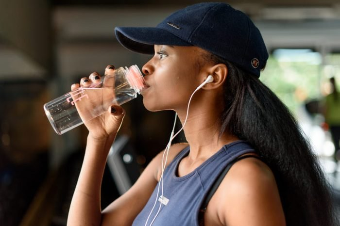 Close-up of black gorgeous woman fitness instructor drinking water during the training exercises in gym
