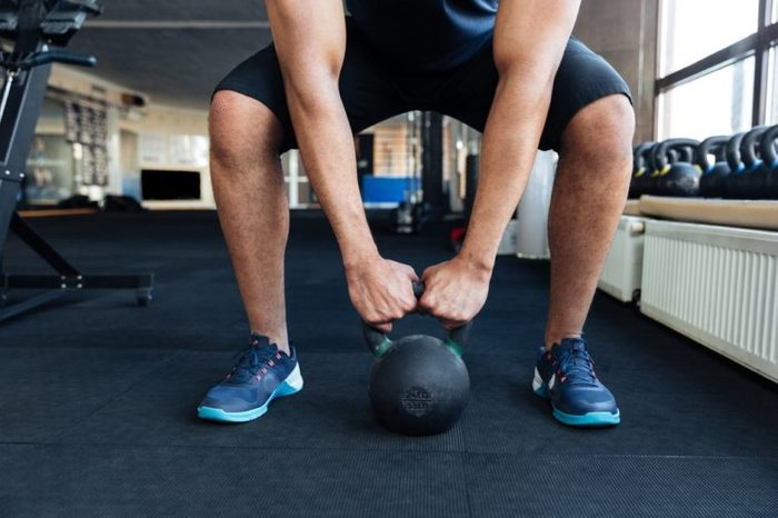 Cropped image of a bodybuilder with kettlebell in a gym, keep kettlebell with two hands
