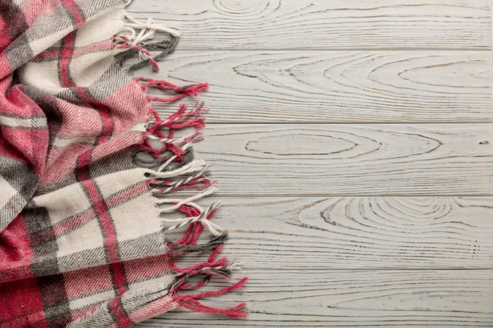 Plaid on a light wooden background. Top view. Flat lay.