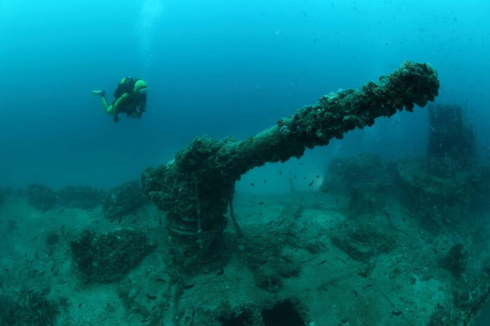 Shipwreck of the Torpedo boat Giuseppe Dezza and scuba diver underwater in the Mediterranean Sea