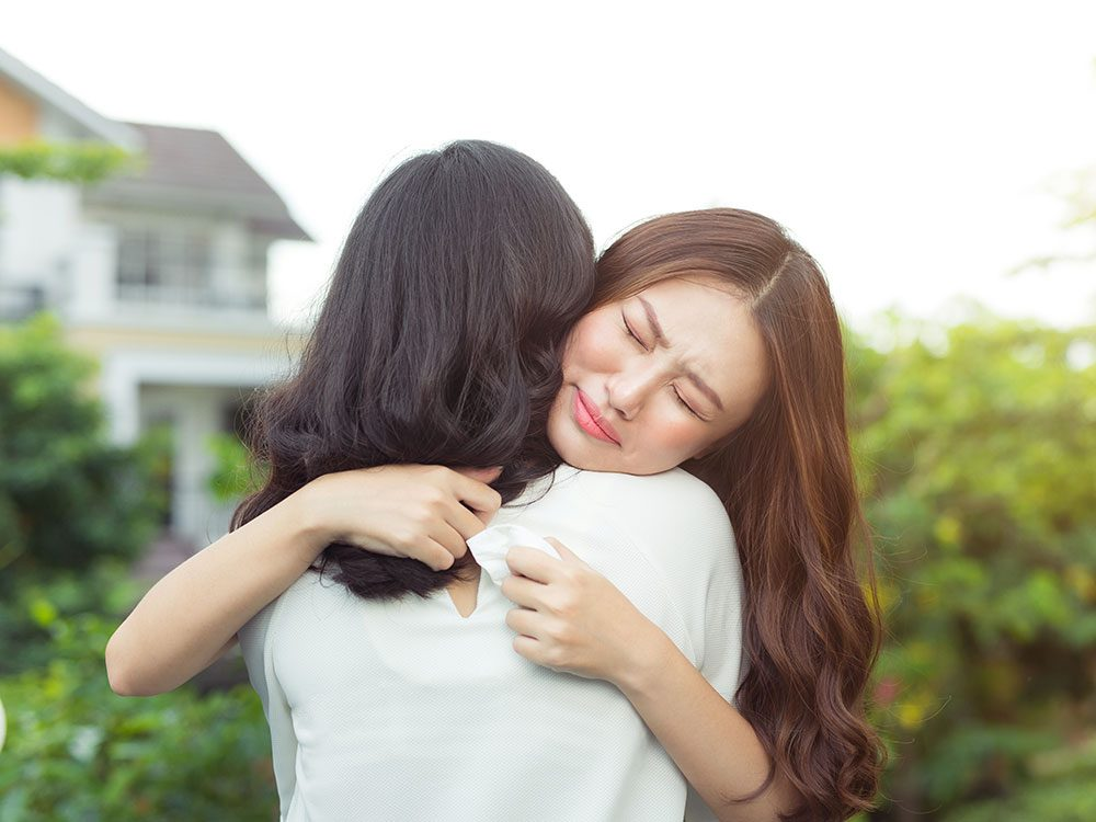 Asian woman hugging friend