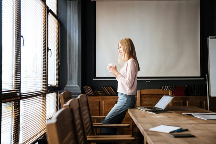 Image of pretty young lady standing in cafe drinking coffee and looking aside while work with laptop.