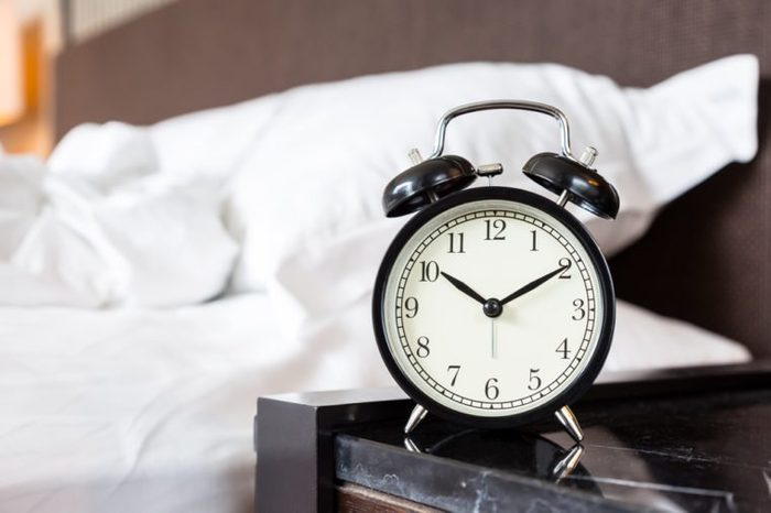 Alarm clock on bed side table