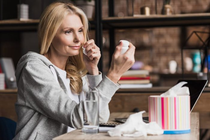 smiling middle aged woman looking at container with medication while sitting at home