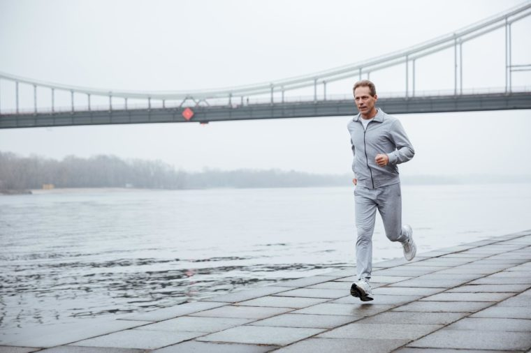 Middle-aged man running on waterfront