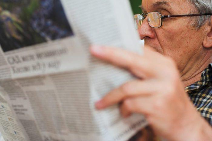 Caucasian older businessman reading newspaper