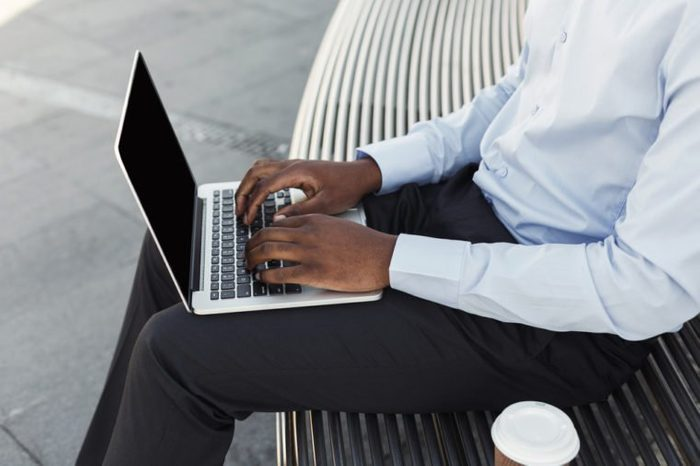 African-american male hands typing on laptop keyboard. Unrecognizable black businessman working on computer with blank screen for copy space. Man sitting on the bench outdoors, having take away coffee