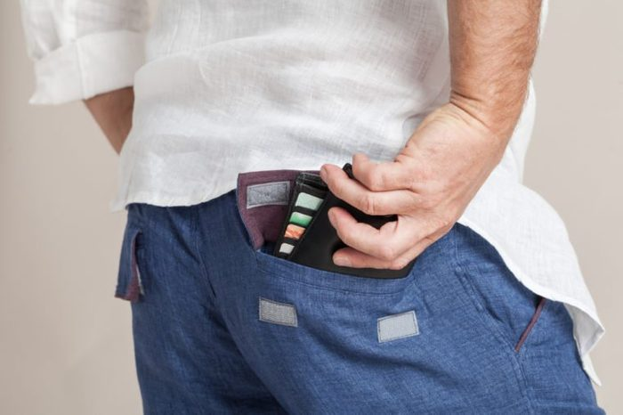 Closeup fashion image of man's hand taking wallet out of his pocket. Body detail of a modern business man. Hand in a pocket with wallet in a loose linen fabric clothes.