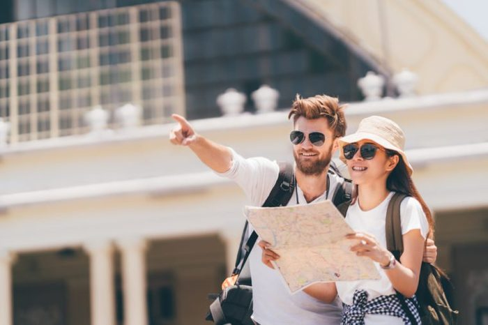Multiethnic traveler couple using generic local map together on sunny day, man pointing toward copy space. Honeymoon trip, backpacker tourist, Asia tourism, or holiday vacation travel concept.
