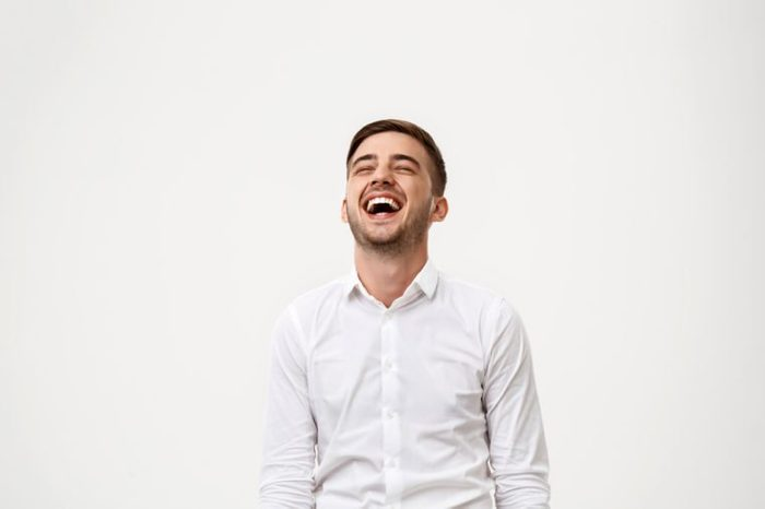 Young successful businessman smiling, laughing over white background.