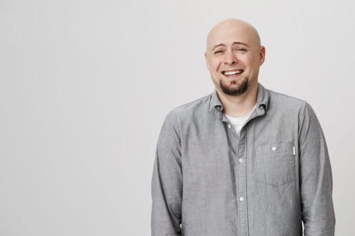 Waist-up portrait of Caucasian good-looking hairless male model with beard dressed in casual clothes posing indoors, laughing at someone`s joke during conversation. Man expressing positive emotions