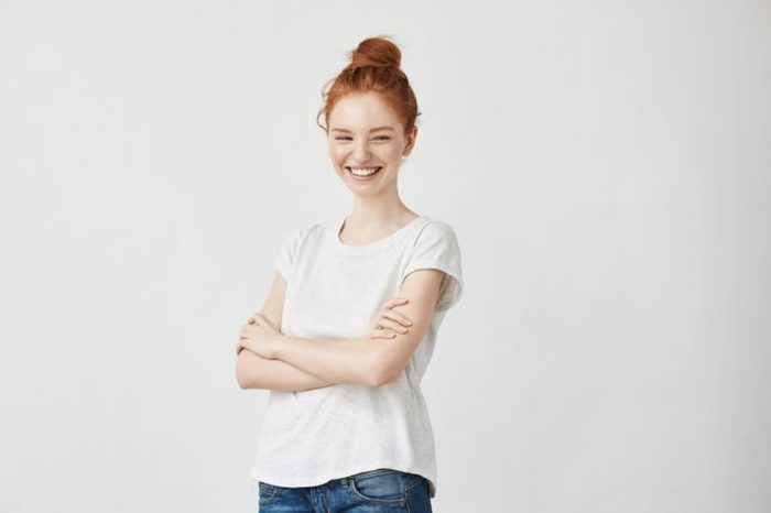 Portrait of happy young beautiful ginger girl laughing. Off camera. Copy space. Isolated on white.