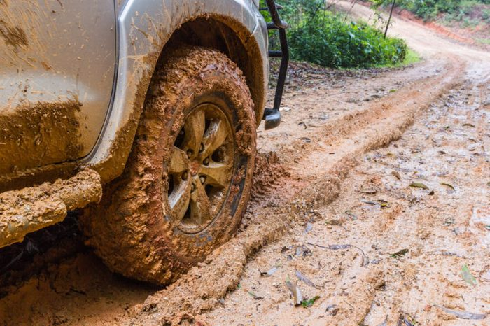 Wheel closeup in a countryside landscape with a muddy road