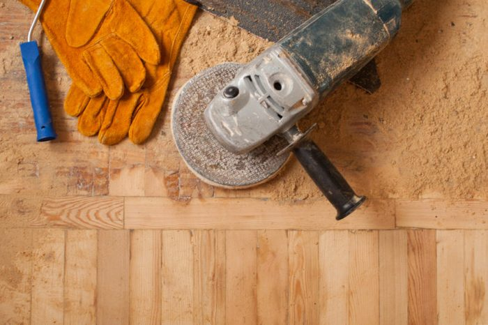 home renovation, parquet sanding, polishing. repair in the apartment. New home. working gloves. The polished wood working. Old working tools. Many working tools on a wooden background.