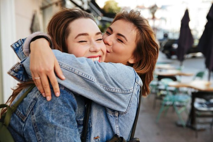 Close-up photo of two emotional happy woman friends hugging each other on city street