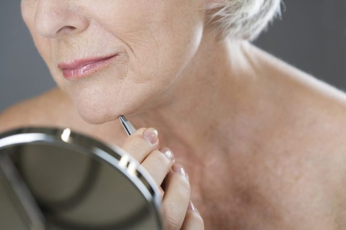 A senior woman plucking hairs from her chin with tweezers