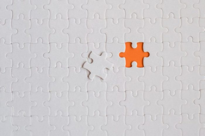 White details of jigsaw puzzle on orange background.
