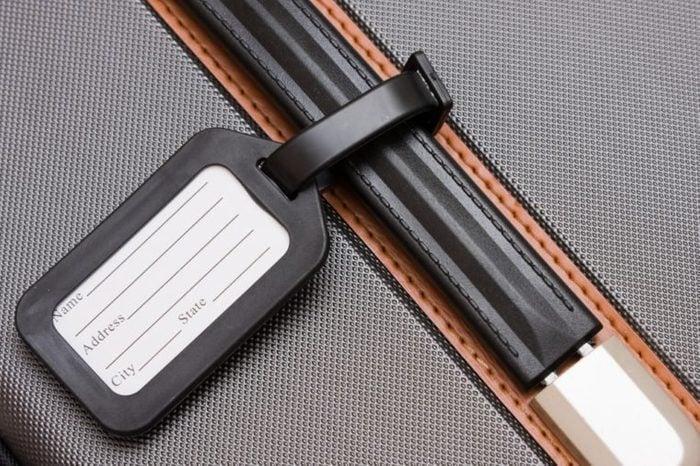 A black luggage tag on a handle on a bag