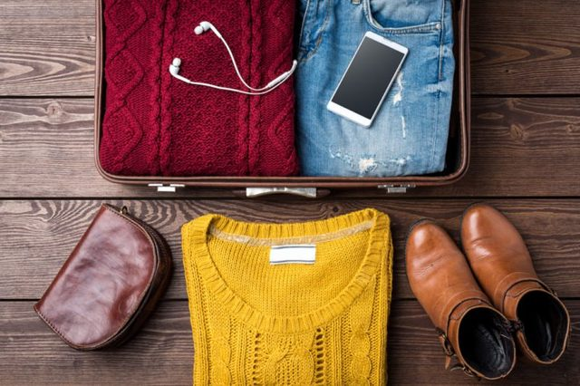 Open suitcase with casual female winter clothes on wooden table. Top view