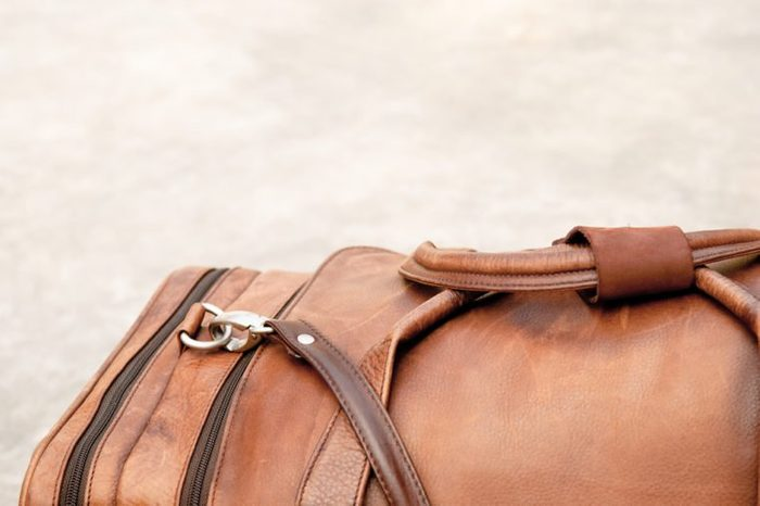brown leather duffle bag on the floor