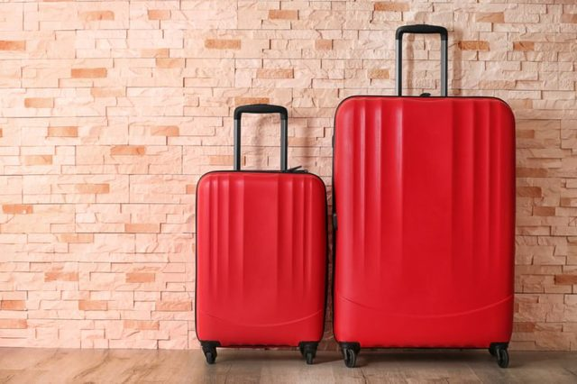 Red suitcases on brick wall background
