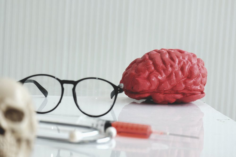 Artificial human brain with skull model medical with syringe in laboratory