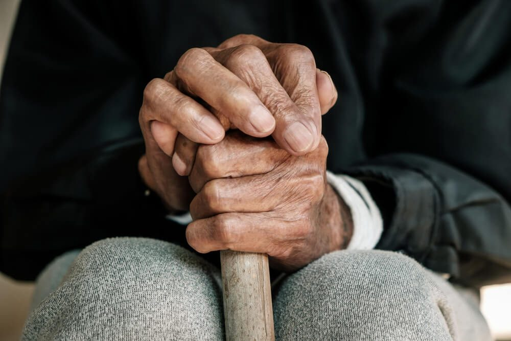 Close-up of elderly hands holding cane