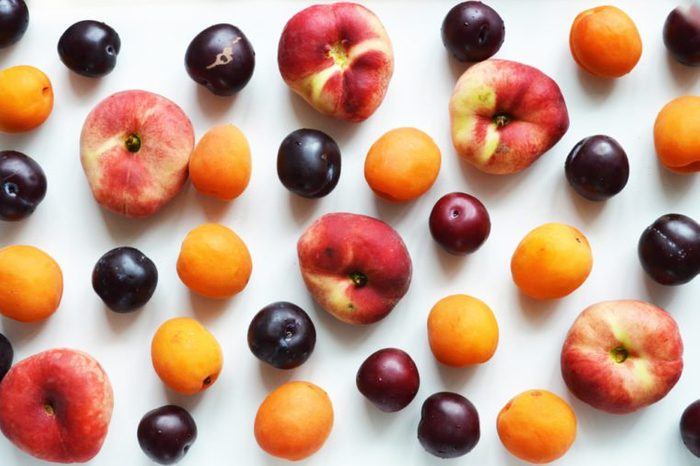 Delicious ripe summer fruits on a white background. Composition of peaches, plums, apricots. View from above.