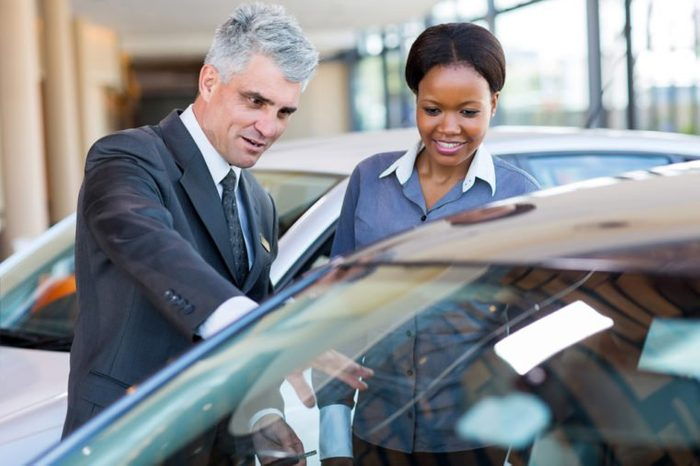 friendly mature car dealer showing new car to african customer