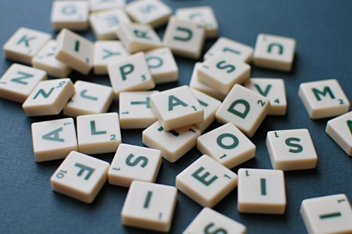 Scrabble game letters on green background.