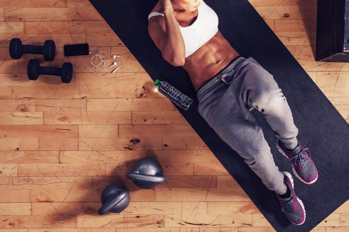Top view of muscular woman doing sit-ups. Female lying on exercise mat doing stomach workout with gym equipments in floor.