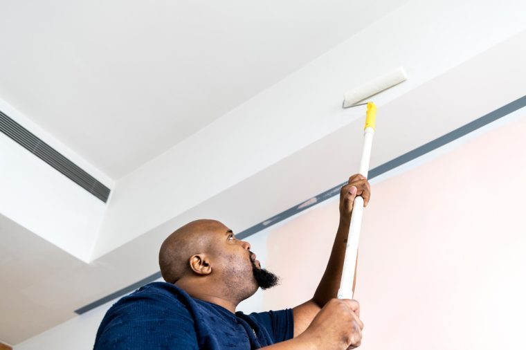 Construction worker painting wall of residence