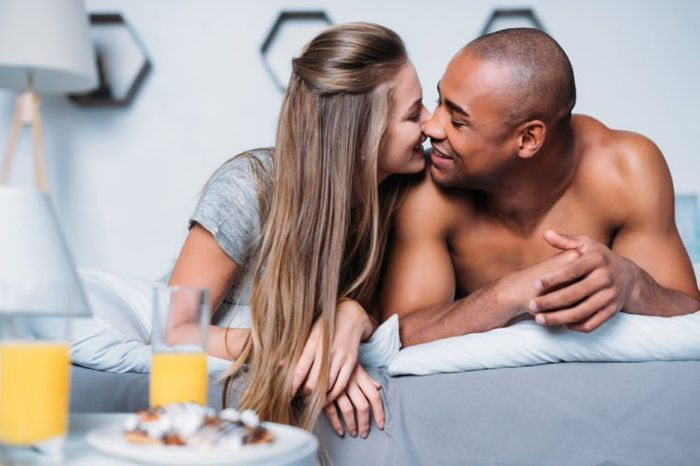 multicultural couple kissing and lying on bed