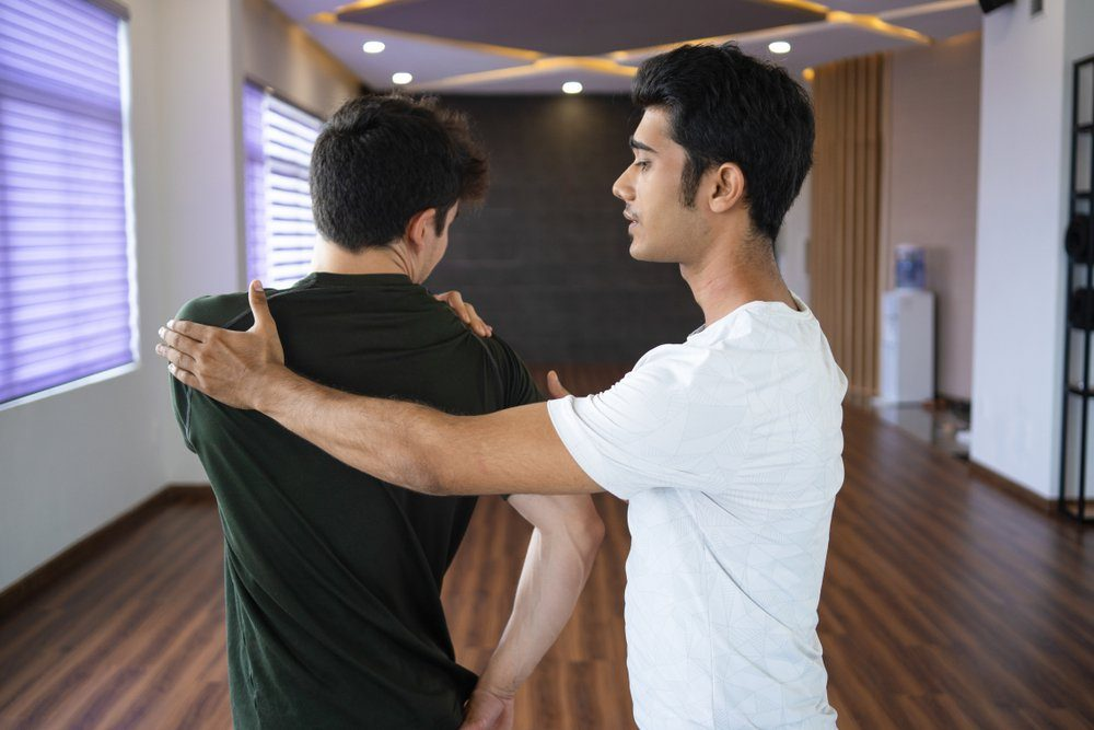 Indian instructor helping beginner at yoga class. Man doing spinal twist in gym. Personal yoga instructor concept.