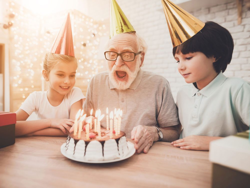 Grandchildren blowing birthday candles with their grandpa