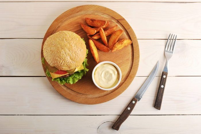 burger with Idaho potatoes and cheese sauce on a round wooden Board and a knife and fork on wooden background - top view