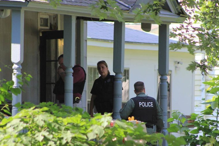 Police officers on porch of home