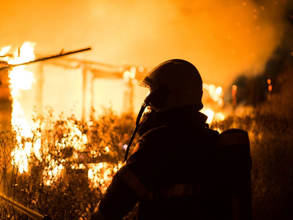 Silhouette of firefighter against flames