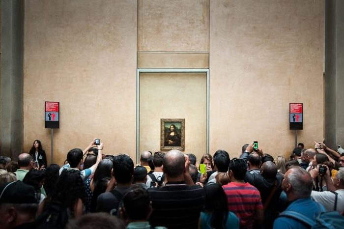 "PARIS, FRANCE - JUNE 18 , 2014 : A many of visitors take photos of ""Mona Lisa"" , by Leonardo DaVinci's at the Louvre Museum, june 18, 2014 in Paris, France."