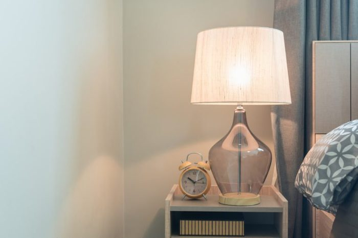 classic lamp on wooden table side in modern bedroom, interior design concept