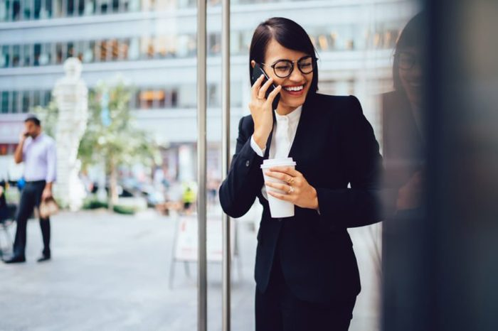 Prosperous female employee enjoying coffee break while talking on smartphone near office. Cheerful happy businesswoman in corporate wear laughing during mobile conversation outdoors in city downtown