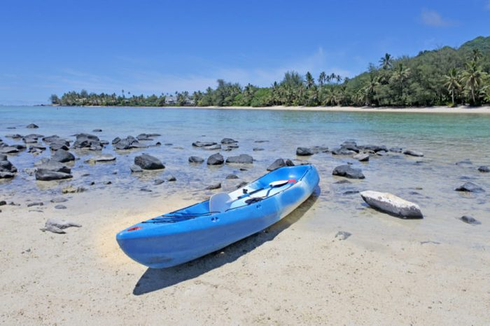 One empty blue kayak on Muri beach lagoon in Rarotonga, Cook Islands