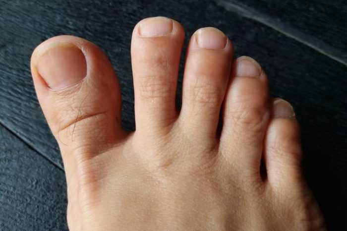 bare foot, asian woman foot on black wooden floor